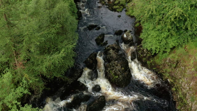 aerial view of fast moving water in a small scottish river in rural dumfries and galloway, south west scotland - johnfscott stock videos & royalty-free footage
