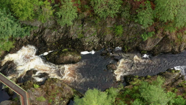 aerial view of fast moving water in a small scottish river passing under a footbridge in rural dumfries and galloway, south west scotland - johnfscott stock videos & royalty-free footage