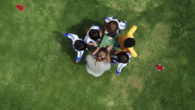 aerial view of female coach explaining plays on board to her soccer team of kids - summer camp stock videos & royalty-free footage
