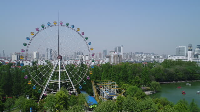 aerial view of ferris wheel and cityscape - ferris wheel stock videos & royalty-free footage