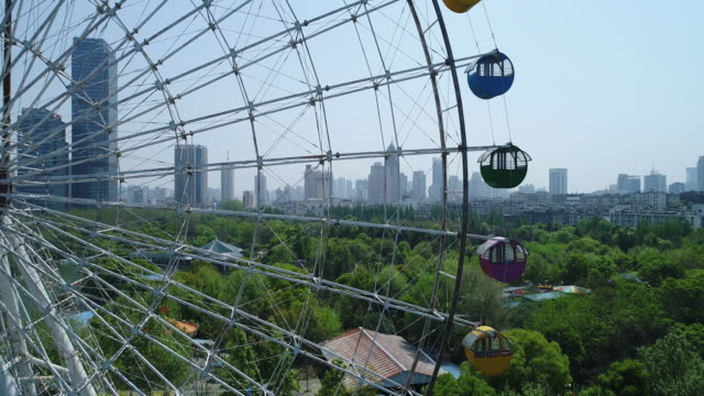 vídeos de stock, filmes e b-roll de aerial view of ferris wheel and cityscape - eco tourism