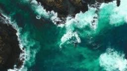 Aerial view of fierce waves splashing against rocks.
