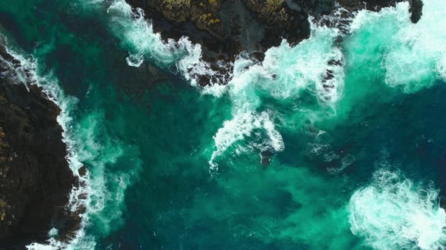 aerial view of fierce waves splashing against rocks. - abstract stock videos & royalty-free footage
