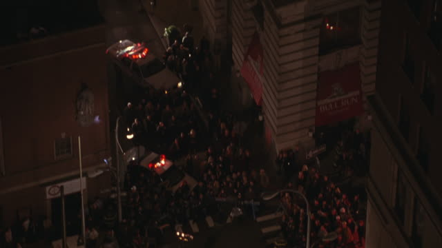 Aerial view of firefighters running through a crowd of bystanders assembled on a street.
