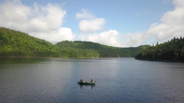vídeos de stock e filmes b-roll de aerial view of fishermans fishing from a boat on lake - captura de peixe