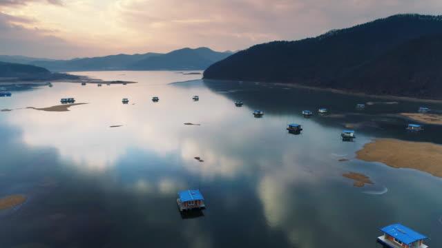 vídeos de stock e filmes b-roll de aerial view of fishing houses in winter at idongjeosuji reservoir - barco casa