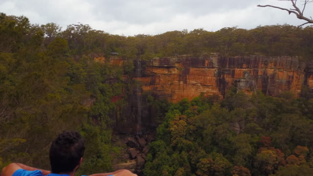 4k aerial view of fitzroy falls with a man looking to the waterfalls, new south wales, australia - ニューサウスウェールズ州点の映像素材/bロール