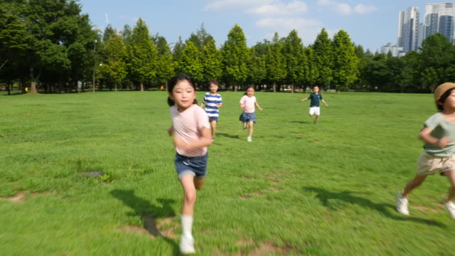 aerial view of five children doing track and field in summer at seoulforest (the third largest park in seoul city) - 芝生点の映像素材/bロール