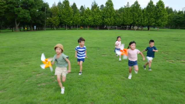 vídeos de stock e filmes b-roll de aerial view of five children running with pinwheels in summer at seoulforest (the third largest park in seoul city) - 4 5 anos