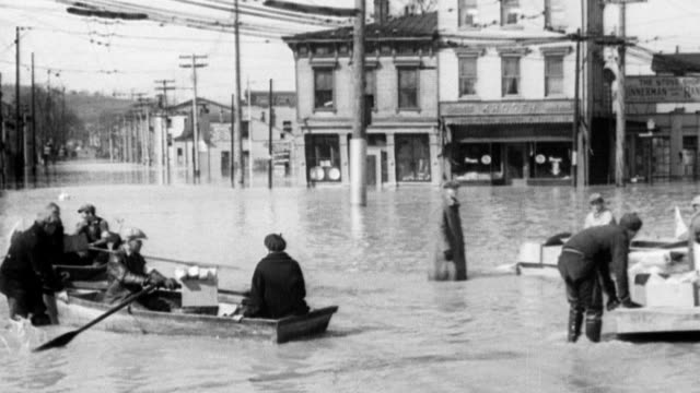 Aerial view of flooded city / CU high flood waters on city street / man in boat rows past collapsed building / men in boats trying to move boxes of...