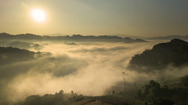aerial view of fog rolls across flowing over rain forest mountain in the northern thailand,hyper lapse - tropical rainforest stock videos & royalty-free footage
