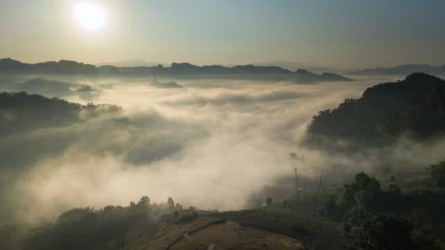 vídeos de stock e filmes b-roll de aerial view of fog rolls across flowing over rain forest mountain in the northern thailand,hyper lapse - ensolarado
