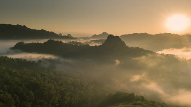 aerial view of fog rolls across flowing over rain forest mountain in the northern thailand,hyper lapse - hill stock videos & royalty-free footage