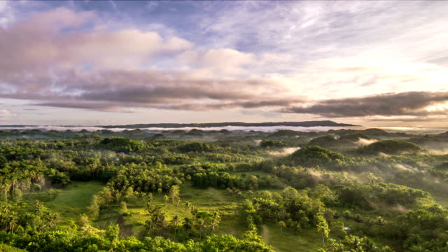 aerial view of foggy chocolate hills in bohol island - philippinen stock-videos und b-roll-filmmaterial