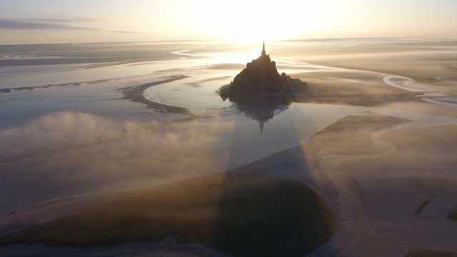 vidéos et rushes de aerial view of foggy sunrise in mont saint-michel by drone - bras de mer mer