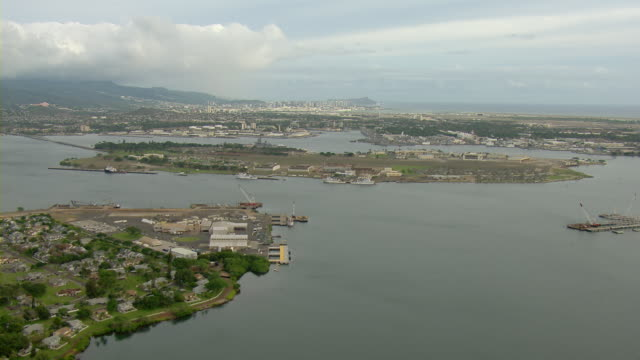 aerial view of ford island in pearl harbor with honolulu, hawaii in the distance. - pearl harbor stock videos and b-roll footage