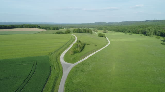 vidéos et rushes de aerial view of fork in the road in rural landscape with agricultural fields. franconia, bavaria, germany, europe. - croisement