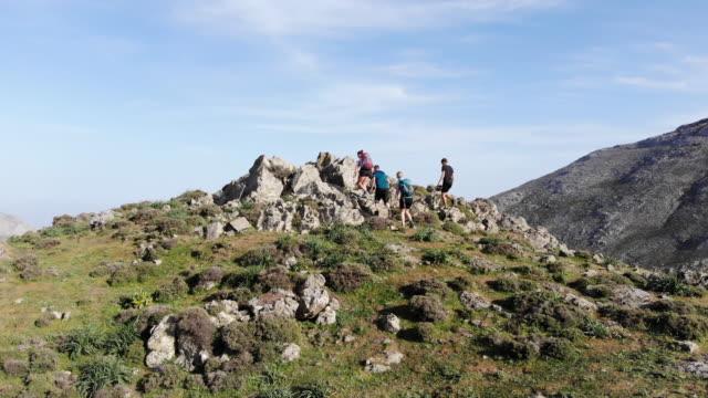 vidéos et rushes de vue aérienne de quatre randonneurs escalade hauteur finale au sommet de la montagne avec vue sur l'océan - grèce