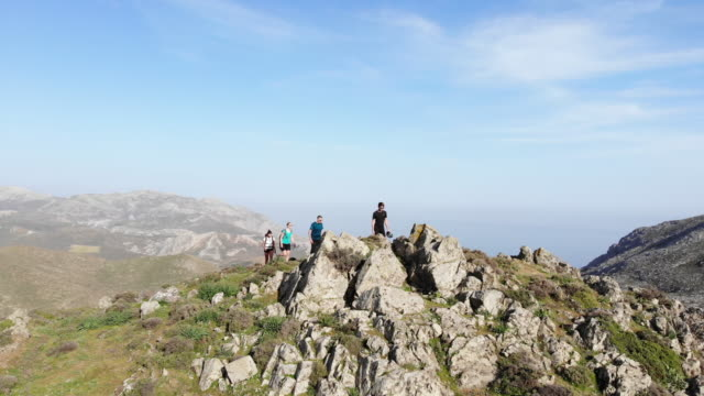 aerial view of four hikers enjoying spectacular panoramic view from mountaintop - greece stock videos & royalty-free footage