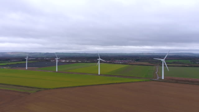 aerial view of four wind turbines spinning - power station stock videos and b-roll footage