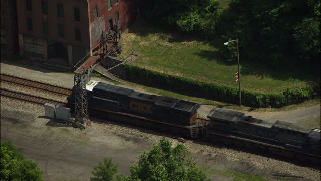 aerial view of freight train passing abandoned building in former coal mining town - appalachen region stock-videos und b-roll-filmmaterial