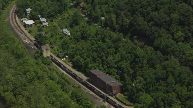 aerial view of freight train passing through former coal mining town - appalachen region stock-videos und b-roll-filmmaterial