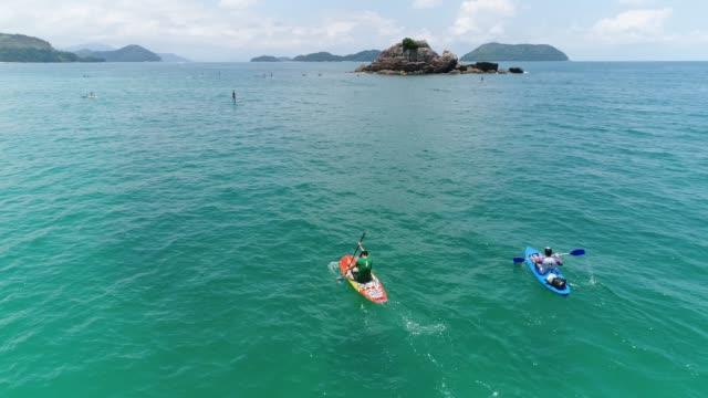 vídeos de stock, filmes e b-roll de vista aérea de amigos praticando esportes no oceano - aventura