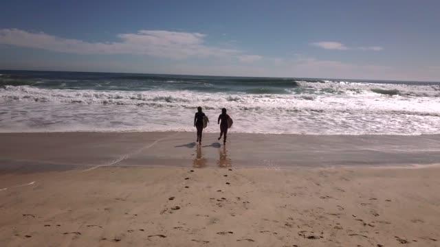 vídeos y material grabado en eventos de stock de vista aérea de amigos caminando por la costa con tablas de surf - gold coast