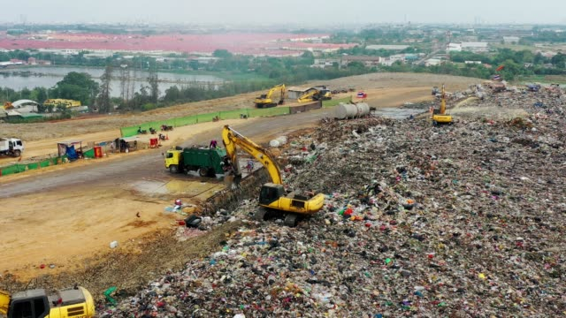 aerial view of garbage truck moves trash in a landfill site or garbage dump, pollution, global warming - dump truck stock videos & royalty-free footage
