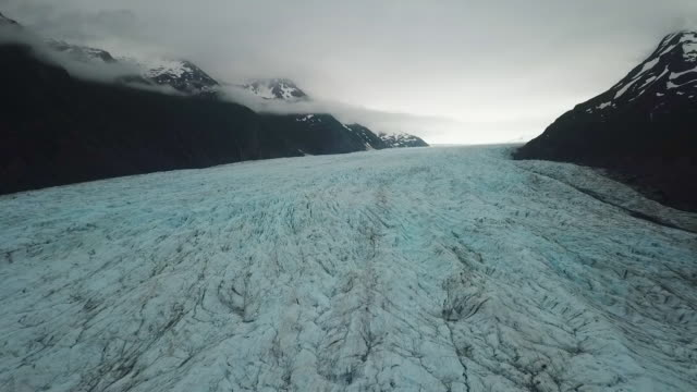 Aerial View of Glacier Ice Between Dark Mountains