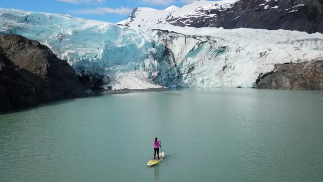 aerial view of glacier & woman on sup in cove - using a paddle stock videos & royalty-free footage