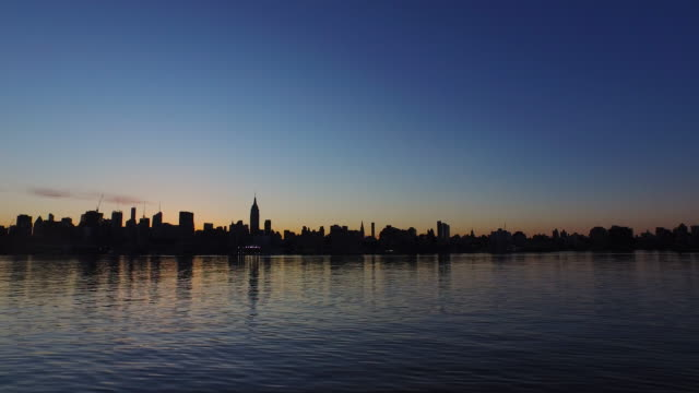 Aerial view of glassy Hudson River reflecting darkened New York City skyline at sunrise