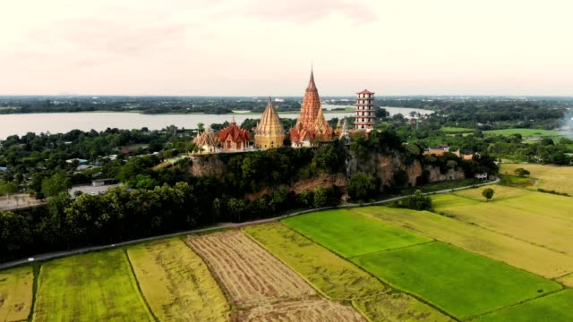 aerial view of golden pagoda on hill with rice paddy plantation at kanchanaburi, thailand - top garment stock videos & royalty-free footage