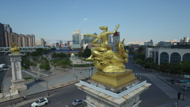 Aerial view of golden statue and traffic on the road