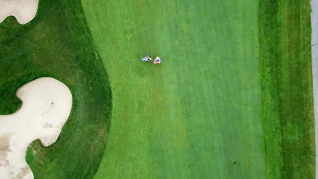 aerial view of golfers walking down the fairway - golfer stock videos & royalty-free footage