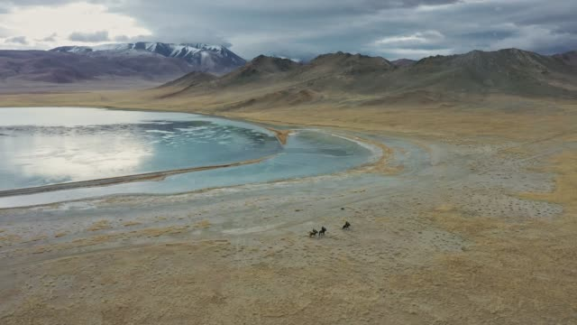 aerial view of group of eagle hunters near the lake in mongolia - indigenous culture stock videos & royalty-free footage