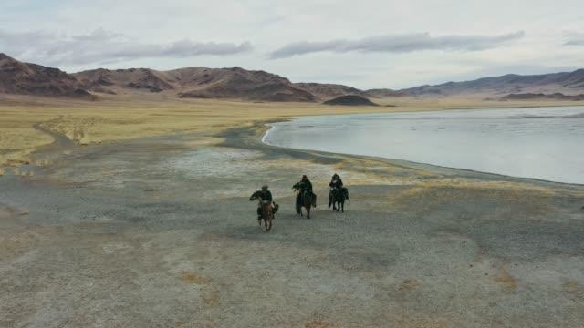 モンゴルの湖の近くのワシハンターのグループの空中写真 - 遊牧民族点の映像素材/bロール