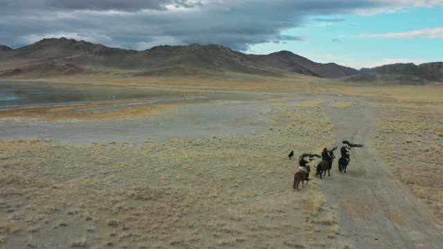 vídeos de stock e filmes b-roll de aerial view of group of eagle hunters near the lake in mongolia - leste