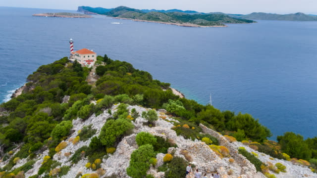 WS Aerial View of group of friends climbing rocky hill on island with lighthouse