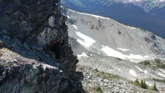 aerial view of guide belaying female mountaineer up rocky precipice - endast unga kvinnor bildbanksvideor och videomaterial från bakom kulisserna