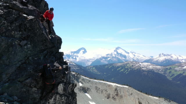aerial view of guide belaying female mountaineer up rocky precipice - climbing rope stock videos & royalty-free footage