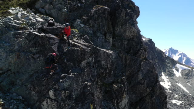 aerial view of guide belaying female mountaineer up rocky precipice - rock stock videos & royalty-free footage