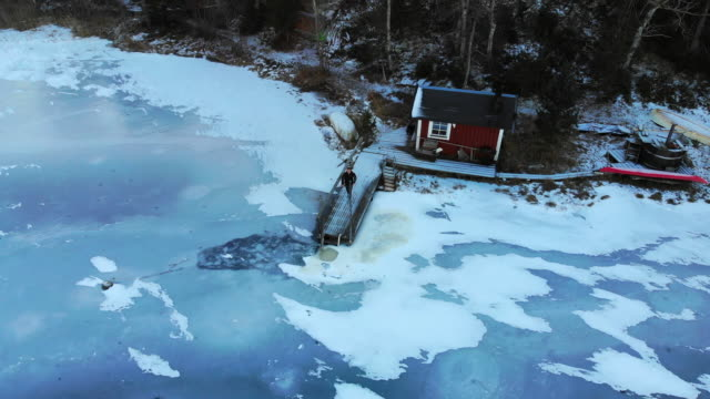 aerial view of guy in a beautiful red cottage with sauna, pier and frozen lake in sweden. - サウナ点の映像素材/bロール