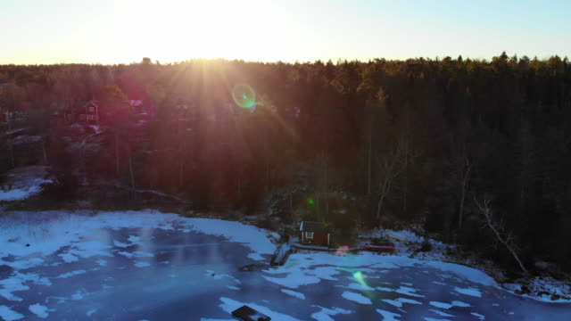 aerial view of guy in a beautiful red cottage with sauna, pier and frozen lake in sweden. - スウェーデン点の映像素材/bロール