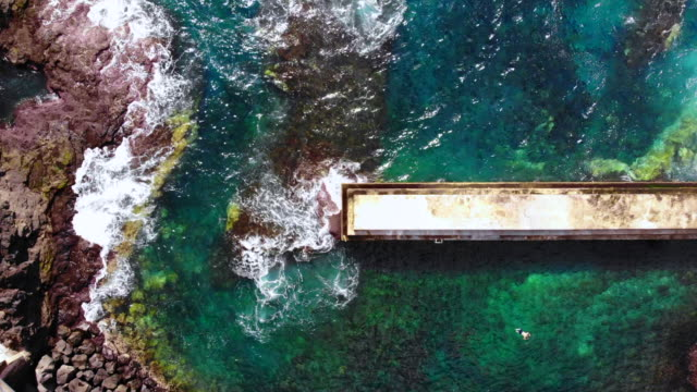 vidéos et rushes de aerial view of guy swimming in artificial beach with pier and concrete in the azores islands. - îles de l'atlantique