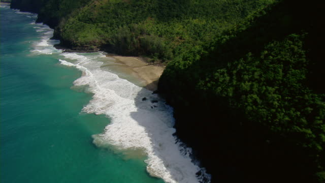 aerial view of hanakapiai beach and lush rocky slopes of the hawaiian island of kauai. - isola di kauai video stock e b–roll