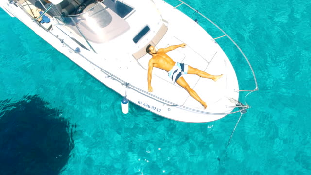 aerial view of handsome man lying in a yatch in amazing, unspoiled and idyllic beach - silvestre video stock e b–roll