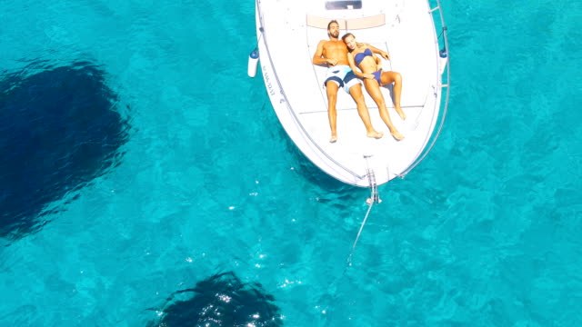 aerial view of handsome man lying in a yatch in amazing, unspoiled and idyllic beach - silvestre stock-videos und b-roll-filmmaterial