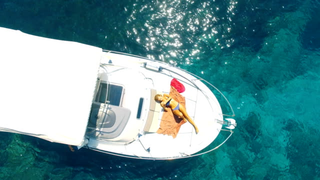 aerial view of handsome man lying in a yatch in amazing, unspoiled and idyllic beach - sunbathing stock videos & royalty-free footage