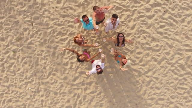 stockvideo's en b-roll-footage met luchtfoto van het 4k van happy vrienden drinken bier op strand - beer alcohol
